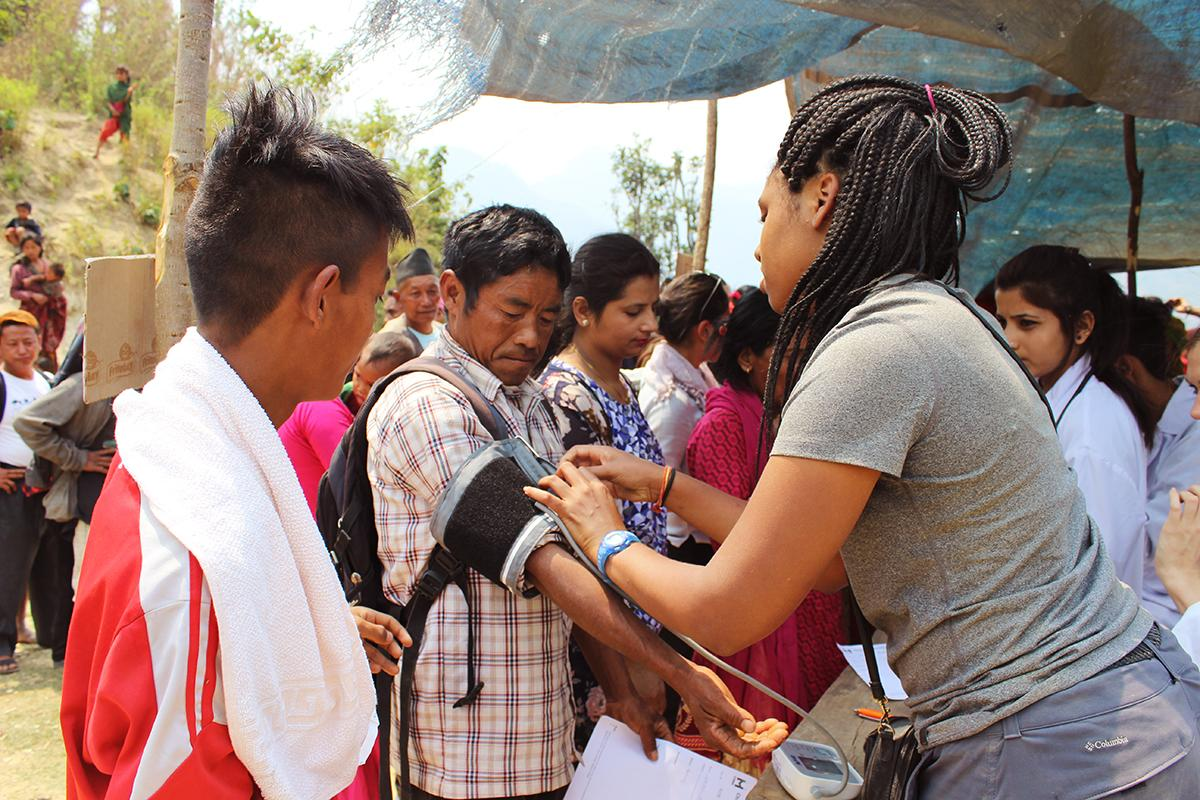 Female intern is pictured taking blood pressure of local during her nursing internship in Nepal with Projects Abroad.